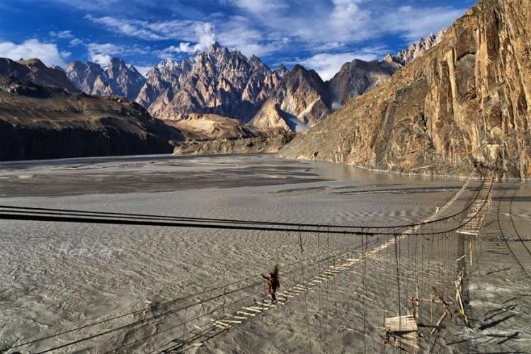 Hussaini brug, aan Borit Lake, Pakistan: ze hangt wel niet boven een ravijn, maar dat maakt deze brug daarom niet minder eng. De dubieuze stevigheid maakt de kans groot dat je er van af dondert en in het water terecht komt. Helaas is het de enige manier om aan de overkant van het meer te geraken. Wie er omheen wilt, is gemakkelijk zo'n vier uur onderweg. © Herbert Wong