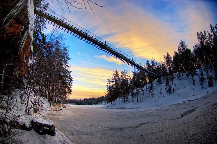 Lapinsalmi hangbrug in Repovesi National Park, Finland: deze brug hangt in natuurpark Repovesi in het Finse Valkeala. In de winter kun je nog over het ijs lopen, maar in de zomer moet je via bruggetjes naar de overkant. © Antti-Jussi Liikala