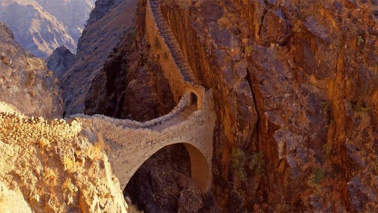 Shaharah brug in Yemen: het dorp Shaharah ligt op een berg op een hoogte van 2.600 meter en kan bereikt worden via verschillende uitdagende paden. De Shaharah brug, gebouwd aan het begin van de 17e eeuw, beschermt het dorp tegen Turkse indringers. Volgens een eeuwenoude legende zouden de inwoners de brug binnen een paar minuten kunnen afzetten. Eenmaal boven krijg je een mooi uitzicht over de vallei. © Alfio Cioffi