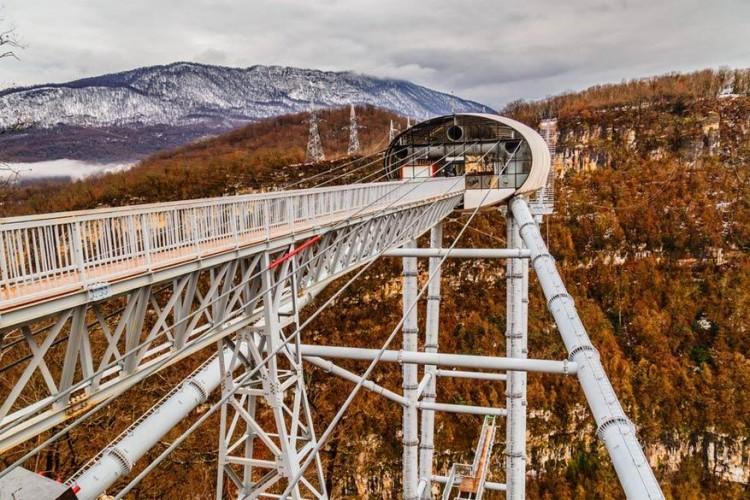 SkyBridge in Sotsji, Rusland: de langste voetgangersbrug in Rusland meet bijna 1 kilometer en kan maar liefst 30.000 mensen tegelijkertijd dragen. Ze strekt zich uit over de Krasnaya Polyana vallei. Als erover wandelen niet genoeg spanning met zich meebrengt, kun je er ook van bungeejumpen of ziplijnen. © Nikolaj Bizyukov