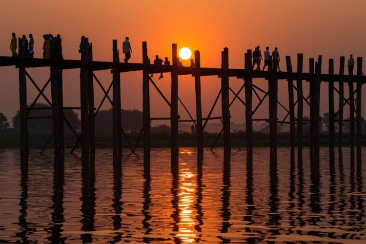 U Bein brug, Myanmar: deze houten brug is bijna 150 jaar oud en een van de meest gefotografeerde dingen in Myanmar. Ze is 1,2 km lang en daarmee de langste teakhouten brug ter wereld. De brug loopt over het Taungthmanmeer en kreeg de naam van de burgemeester die het liet bouwen. 's Avonds flaneert de plaatselijke bevolking er op en verkopen de wachthuisjes op de brug van alles en nog wat. © Sergey Laybold
