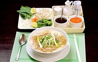Phở Hà Nội: Hanoi is de thuisstad van phở en daar houden ze het simpel. De bouillon blijft helder op een zichtbaar laagje olie na, maar moet vol smaak zitten. De enige garnituur bij de dampende kom zijn kleine schoteltjes met taugé, partjes limoen en gehakte chili. © Cơ Khí Viễn Đông