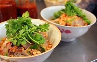 Phở Tíu: dit gerecht komt uit Hanoi, heeft Chinese roots en is in tegenstelling tot ander varianten geen soep. Wie dit bestelt, krijgt noedels overgoten door een dikke op varkensvlees gebaseerde jus met plakjes varkensgebraad, taugé, verse kruiden, pinda's, gedroogde sjalotten en een scheutje azijn. © Theo Diệu Hương