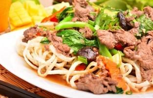 Phở Xào: deze noedels worden kort gefrituurd in hete olie om ze daarna te laten rusten op een vlakke plaat. De rest van de ingrediënten, gesneden rundsvlees (gemarineerd in oestersaus en sesamolie), wortels, paksoi, gesneden uien, taugé en sjalotjes, worden geroerbakt in een luchtige donkere sojasaus. © Papayavn.eu