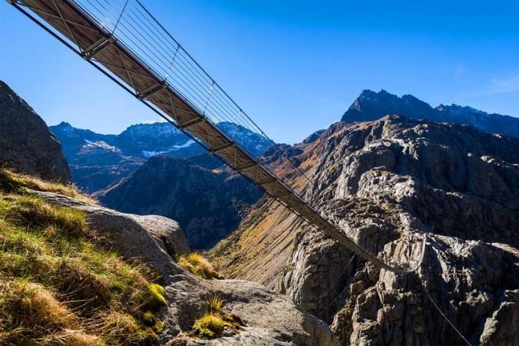 Trift hangbrug in Gadmen, Zwitserland: door de snelle opwarming van het klimaat smolt de Triftgletsjer sneller en kon je er niet meer al wandelend over lopen. Vandaar werd in 2009 deze 170 meter lange burg, tevens de langste voetgangersbrug in de Alpen gemaakt naar een Nepalees ontwerp. De brug bereiken kan enkel met een kabelbaan of een wandeling van anderhalf uur. Eenmaal daar, steek je het gletsjermeer over op 100 meter hoogte. © jhribarfoto