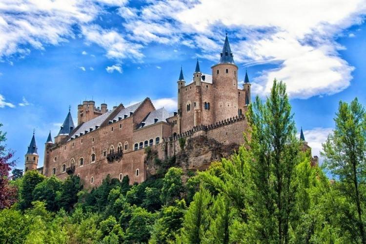 Alcázar van Segovia in Spanje: de stad en het kasteel zijn gebouwd op een driehoekige bergtop bij de samenloop van de rivieren Eresma en Clamores. De bouw startte in de 11de eeuw onder koning Alfonso VI. Vandaag is de plek een van de belangrijkste attracties in de Segovia en een van de bekendste historische sites van het land. © Jose Francisco