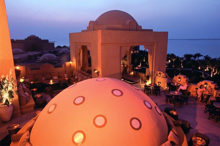 One & Only Royal Mirage in Dubai, Verenigde Arabische Emiraten: de lucht is het plafond op Roof Top, het dakterras van dit hotel. De cirkelvormige bar heeft een ontspannen atmosfeer. De overvloed aan geborduurde kussens en kaarsen creëert warmte en intimiteit in de magische en muzikale bar waar tot laat in de nacht oriëntaalse cocktails worden geserveerd. © One & Only Royal Mirage