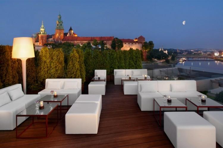 Sheraton Grand Hotel in Krakau, Polen: dit hotel is ideaal gelegen aan de Wislarivier, dicht bij het bekende Wawel kasteel in Krakau. Op het uit glas opgetrokken dakterras kun je die twee trekpleisters het best bewonderen. Op tien minuten ben je trouwens van dit hotel naar het Marktplein in de Oude Stad en het bekende district Kazimierz. © Sheraton Grand Hotel Krakow