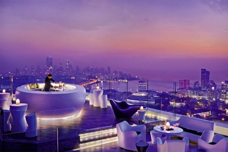 Four Seasons Hotel in Mumbai, India: de openluchtbar Aer op het dak van dit hotel start elke avond met een 'Sunset Happy Hour' van 17u30 tot 20u. Dan krijg je hier cocktails en champagne aan de helft van de prijs. Later op de avond geniet je hier van gevarieerde dj-sets. De bar bekleedt het hele dak van het hotel en is de hoogste in India dankzij z'n ligging op de 34ste verdieping. © Four Seasons Hotel