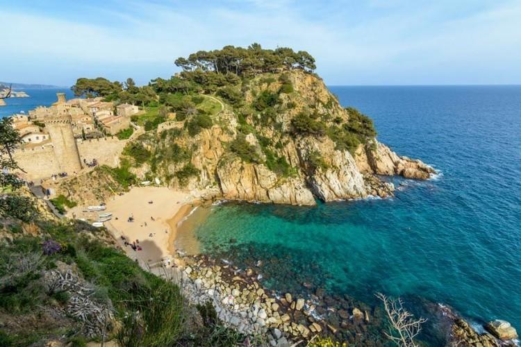 Cala Codolar, Ibiza in Spanje: het zand is er een beetje dof en grijs, maar het water is er diep saffierblauw wat veel goedmaakt. Beschut door kliffen ligt Codolar in de buurt van het populaire Cala Comte in het westen op het eiland. Het is er minder hectisch en de strandbar serveert frisse eenvoudige drankjes aan redelijke prijzen wat ongebruikelijk is in Ibiza. © Albert