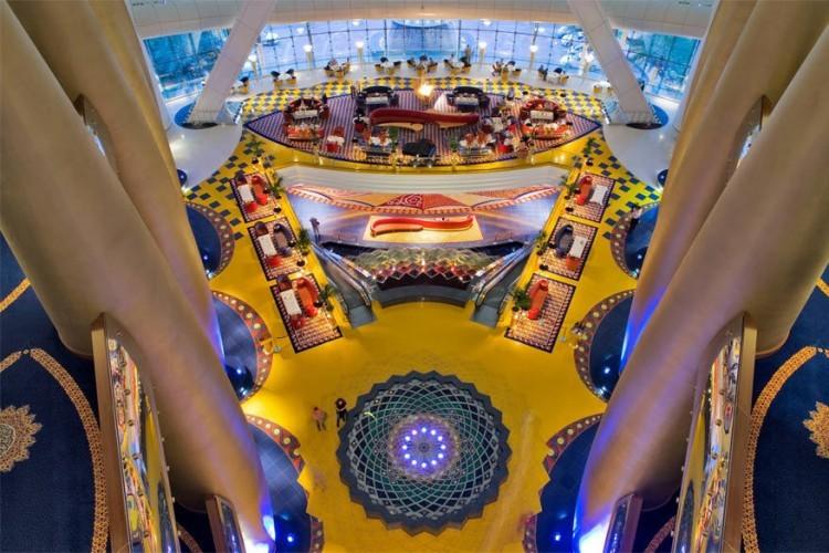 Burj Al Arab in Dubai, Verenigde Arabische Emiraten: bereid je voor om helemaal versteld te staan in de lobby van 's werelds meest luxueuze hotel. Met de hulp van kleurrijke islamitisch geïnspireerde kunst, details van bladgoud in 24-karaat, een heuse waterval, een veelkleurig atrium (ook het langste van de wereld) en twee aquariums heeft het Burj Al Arab hotel zichzelf echt overtroffen. © Burj Al Arab