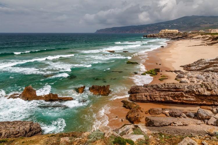 Guincho, Cascais in de buurt van Lissabon, Portugal: net langs de kustlijn van Estoril vanuit Lissabon liggen een reeks gouden zandstranden. Vermijd de drukte in het populaire Cascais, maar ga verder naar het Serra de Sintra Nationaal Park, waar je Praia da Guincho vindt. Ideaal voor ervaren wind- en kitesurfers omwille van de enorme golven en sterke wind. Ook perfect voor een verkwikkende wandeling. Beloon jezelf daarna met lunch in Fortaleza do Guincho. © Andrey Omelyanchuk