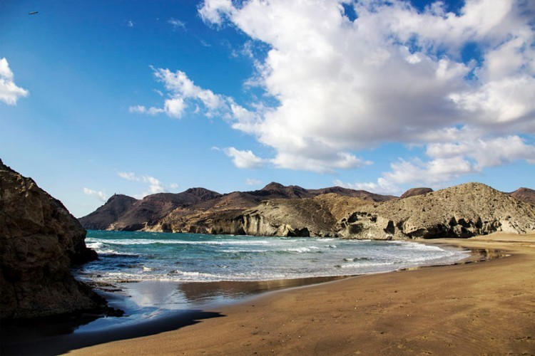 Mónsul, Andalusië in Spanje: Mónsul is een van de vele ongerepte stranden in het Cabo de Gata natuurpark op het zuidelijkste puntje van Spanje. De kleurrijke kliffen, denk: roest, mosterd, mauve, zwart, grijs en wit, omlijnen de kust en ondersteunen wachttorens die over duizenden jaar erin gebouwd zijn om piraten en andere indringers weg te houden. © Miguel Ángel Soto