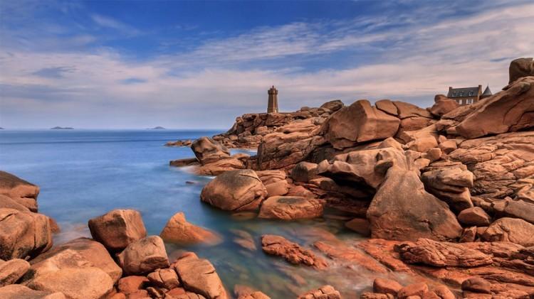 Ploumanac'h, Bretagne in Frankrijk: halverwege langs de noordelijke kant van Bretagne's grillige kustlijn ligt het dorpje Ploumanac'h, in een surrealistisch stenenlandschap van glinsterende rooskleurige rotsen, kliffen en misvormde keien. De meeste bezoekers komen er wandelen op de paden of ravotten in het zand. Het is er aangenaam rustig, zelfs in de zomer. © Nicolas Pommier