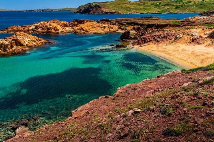 Cala Pregonda, Menorca in Spanje: aan de rustige noordkust van Menorca ligt Pregonda, een lang strand met roodgoud zand en rozige rotsen. Kleine eilanden beschermen de baai waardoor de zee steeds rustig en kristalhelder is. Neem een picknick en genoeg water mee als je er naartoe gaat want er is nagenoeg geen accommodatie. © Gerd Fischer