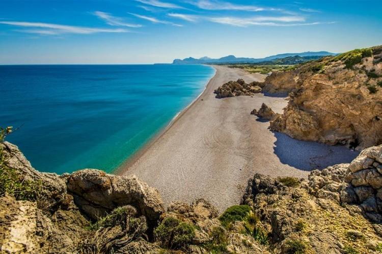 Traganou, Rodos in Griekenland: de gehele zuidoostelijk gelegen, Mediterrane kust van Rodos is bedekt met stranden. Een van de meest afgelegen is het kiezelstrand Traganou. Voorbij een onopvallend militair controlepunt ligt een beschutte baai versierd door de Traganospilia, een trio van grotten die je kan verkennen dankzij ingangen die zowel via het land als de zee lopen. Sijpelend zoetwater houdt de zee hier schoon, maar koeler dan normaal. © Ikoutas Vassilis