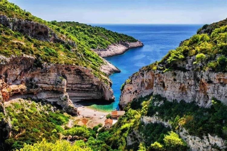 Stiniva, Vis in Kroatië: het afgelegen eiland Vis ligt op twee uur en twintig minuten met de boot van Split. Met slechts twee hoofdwegen is het er gemakkelijk om het lokale leven te ontdekken. Lokale reisbureaus bieden excursies aan naar het binnenland van het eiland en boottochten rond de kust om nog meer gezellige stranden als Stiniva te verkennen. Dit strand is overigens enkel toegankelijk door het steile, smalle pad af te wandelen of met een watertaxi. © Aleksandar Gospic
