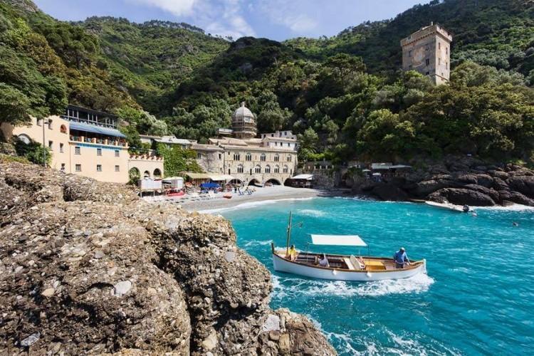 San Fruttuoso, Liguria in Italië: een terras met uitzicht op een idyllische baai met op de achtergrond een middeleeuwse adbij, dat is San Fruttuoso. Met de boot ligt het ergens halverwege Portofino en Camoglio. Om er te geraken wandelen je ofwel door het voorgebergte van Portofino of neem je de ferry. © Rob Kints