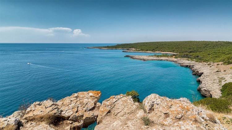 Porto Selvaggio in Puglia, Italië: een plaats van oude, culturele tradities, omgeven door de zee. Er zou in de buurt een geheime baai liggen met de naam 'wilde haven' een paar kilometer ten westen van het gezellige stadje Nardò. Hier kun je overigens zonnebaden op het strand en zwemmen in de zee of verken het pad dat naast de kust kronkelt doorheen geurige struiken. © David Tornese