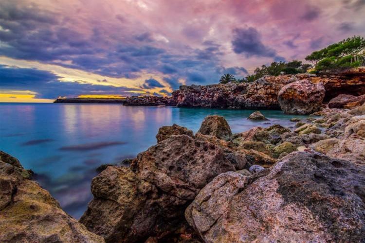 S'illot, Majorca in Spanje: de kleine baai met kobaltblauw water wordt beschut door pijnbomen op het vasteland van Victòria, die de baai van Alcúdia scheidt met die van Pollença in het noordoosten van Majorca. Paden kronkelen tussen de bomen op de heuvels voor diegenen die van een wandeling houden. Je kan een picknick houden op het strand of een paella eten in het S'illot restaurant. © Sebastian Schriever