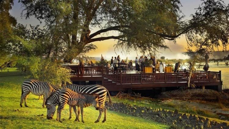 Royal Livingstone in Zambia: gasten die verblijven in dit hotel in Zambia starten hun vakantie allerminst verrassend. In plaats van in te checken aan een balie zoals gebruikelijk worden ze met een watertaxi meegenomen om in te checken bij de aanlegsteiger van het hotel. Daar krijgen ze ook meteen fruitcocktails in hun handen geduwd om diezelfde handen even later te laten masseren. © Royal Livingstone