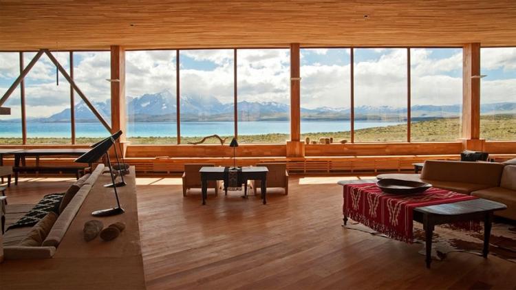 Tierra Patagonia in Chili: dit hotel met 37 kamers en 3 suites ligt op een klif waar de Zuid-Amerikaanse pampa het meer van Sarmiento ontmoet. Interieurarchitecten Alexandra Edwards en Carolina DiPlano wilden de schoonheid van buiten naar binnen brengen. Daar zijn ze goed in geslaagd. De gezellige lounge, bar en lobby hebben ze helemaal opengetrokken waardoor je helemaal van het uitzicht kan genieten via de grote glaspartijen. © Tierra Patagonia