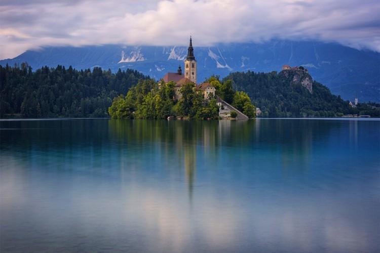 De Maria Hemelsvaartskerk ligt moederziel alleen op een eilandje in het midden van het meer van Bled in Slovenië. Ze werd gebouwd in de 15de eeuw naar een gotische stijl en in 1465 werd de kerk ingehuldigd door de eerste bisschop van Ljubljana, Žiga Graaf Lamberg. In 1509 beschadigde een aardbeving de kerk waardoor ze heropgebouwd moest worden. De huidige bouw dateert uit de 17de eeuw. © Evan Hammonds
