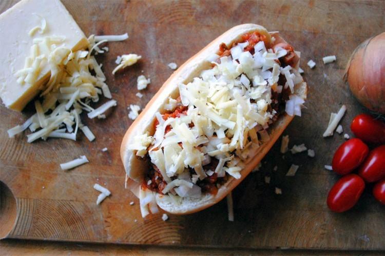 Coney: kleine hotdog in een klein broodje met chili, gesneden ajuin en een hoopje fijn geraspte cheddarkaas. © bimbim101