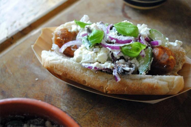 Griekenland: hotdog tussen een broodje afgewerkt met fetakaas, rode ui, olijven en komkommer. © bimbim101