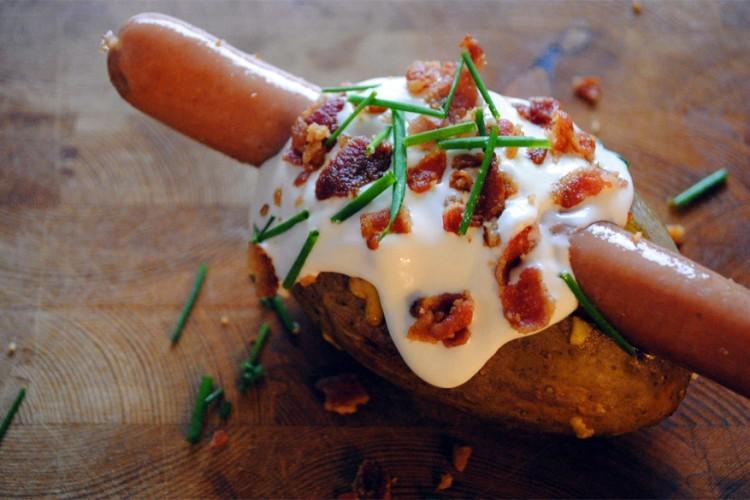 Idaho: hotdog tussen een gekookte aardappel en afgewerkt met stukjes spek, bieslook en zure room. © bimbim101