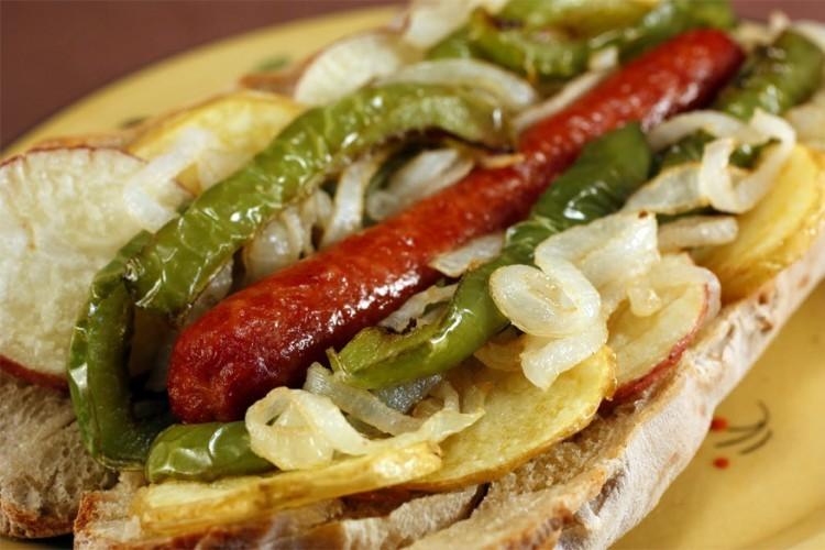 Italië: gefrituurde hotdog in een Italiaans broodje met paprika, ui, frietjes, ketchup en mosterd. © Recipes Hubs