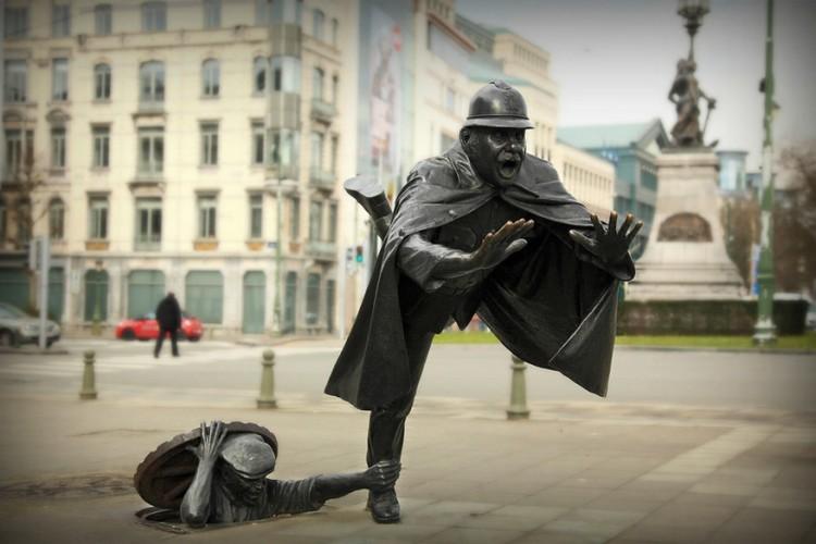 De Vaartkapoen in Brussel, België: dit standbeeld staat sinds 1985 in de Brusselse gemeente Molenbeek. De naam van het kunstwerk verwijst naar iemand die in Molenbeek geboren is. Kunstenaar Tom Frantzen heeft het beeld op twee niveaus gezet: enerzijds het riool en anderzijds de stoep. De Vaartkapoen komt als een duivel uit een doos en doet de autoriteit, zijnde de politieagent, wankelen. © Claude