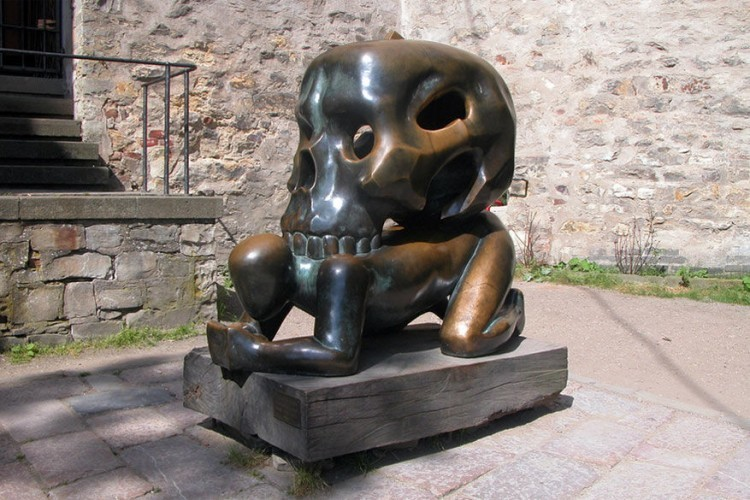 Man and Skull in Praag, Tsjechië: dit bizarre beeldhouwwerk is te vinden aan de bekende bezienswaardigheid Prague Castle. Het zou een eerbetoon zijn aan de schrijver Franz Kafka, al vinden sommigen deze interpretatie eerder een belediging voor de man dan een compliment. © Iuliia Iankiva