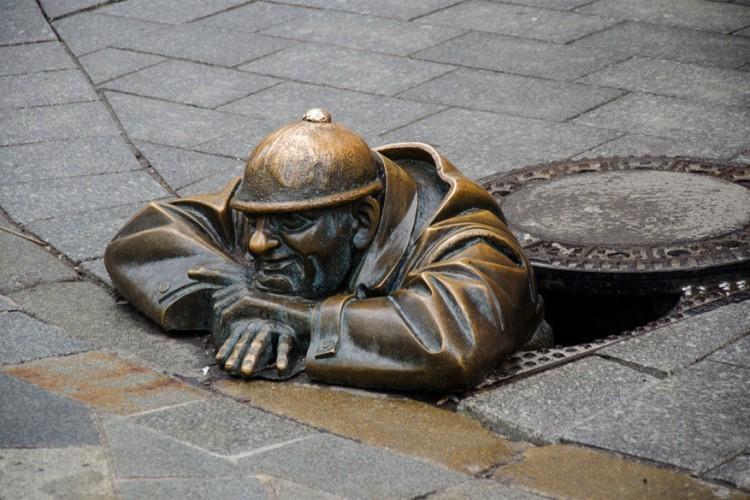 Man at Work in Bratislava, Slowakije: dit bronzen sculptuur van Viktor Hulík beeldt een man, genaamd Čumil uit die uit een rioolgat hangt. Hij zou aan het rusten zijn na werken in het riool, maar hij zou volgens anderen ook onder de rokken van de vrouwen piepen. Leuk detail: nadat het hoofd van het standbeeld er al twee keer afgereden werd door onoplettende bestuurders, staat er nu een gepersonaliseerd verkeersbord bij het kunstwerk. © Volodymyr Osypov