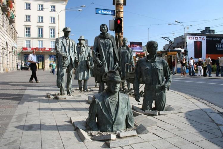 Przejście in Wroclaw, Polen: 'Przejście', wat passage in het Pools betekent, is een set van bronzen sculpturen die zich bevinden op een bekend kruispunt in Wroclaw, gemaakt door de Poolse kunstenaar Jerzy Kaline. Het kunstwerk bestaat uit twee scenes waarbij in het eerste deel zeven mensen uit de grond komen gerezen en in het andere deel net het tegenovergestelde gebeurt. De beeldhouwwerken bestaan sinds 2005 en herdenken de 24ste verjaardag van de krijgswet. © Paul & Kelly