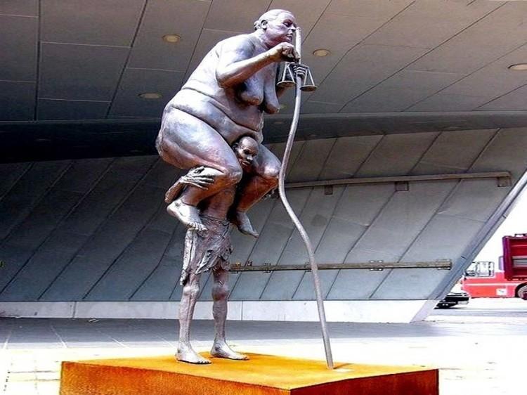 Bureaucratic Themis in Ringkobing, Denemarken: dit sculptuur van de Deense kunstenaar Jens Galschiot beeldt de godin van rechtvaardigheid uit als een obese vrouw steunend op de schouders van een uitgehongerde Afrikaanse man. Het standbeeld is 3,5 meter hoog en was voor het eerst te zien in 2009 tijdens de 15de klimaatconferentie die plaatsvond in Kopenhagen. © Google Plus
