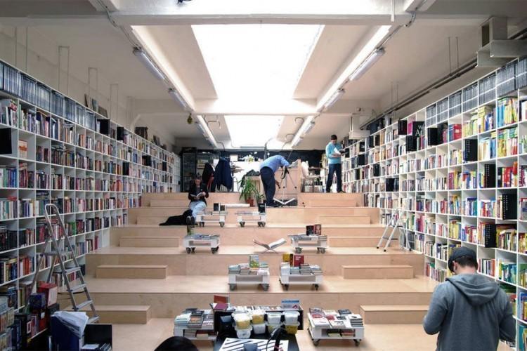 Plural Bookshop in Bratislava, Slovakije: deze plek is niet alleen een boekenwinkel, maar ook een koffiebar waar het aangenaam vertoeven is. De brede trappen maken de ruimte ook ideaal voor concerten, lezingen of projecties. Op het eerste zicht lijkt de boekenwinkel klein, maar de ingenieuze inrichting biedt plaats genoeg voor geïnteresseerden. © Plural Bookshop