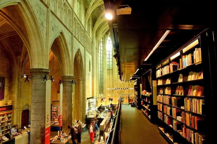 Selexyz Dominicanen in Maastricht, Nederland: deze boekenwinkel vond in 2005 onderdak in het bijzondere decor van een 13de-eeuwse kathedraal. De winkel is opgedeeld in drie etages met helemaal bovenaan een mezzanine met zwarte boekenkasten. De boekenwinkel biedt het grootste aanbod Engelse titels aan in heel Maastricht. Haast je hier vooral niet. Er staan zetels waar je rustig kan kiezen welk boek je mee naar huis wil nemen. © Ulrike Parnow