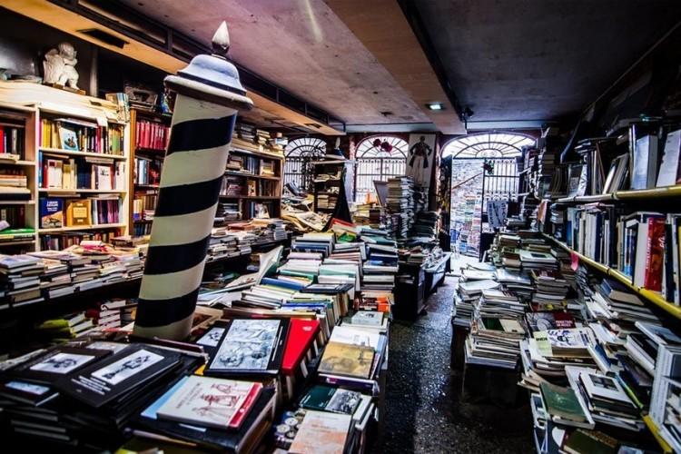 Libreria Acqua Alta in Venetië, Italië: een van de meest originele boekenwinkels ter wereld die elke vrije vierkante centimeter benutten om hun aanbod te tonen. Duizenden nieuwe of tweedehandsboeken versieren de antieke planken of staan zelfs opgesteld in typische houten gondola's. Vergeet zeker geen babbeltje te slaan met eigenaar Luigi Frizzio en zijn vier nieuwsgierige katten. © Aubrey Dunnuck
