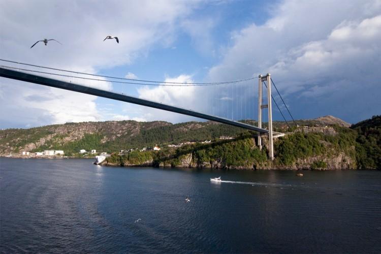 Askøybrug in Noorwegen: via deze brug, met een lengte van iets meer dan 1.000 meter, bereik je vanaf de stad Bergen het eiland Askøy. Het water dat eronder stroomt zijn de Byfjorden. Bij de opening in 1992 was de Askøybrug de langste hangbrug van Noorwegen. Tot de Hardangerbrua die plaats wegkaapte in 2013. © Leonardo via Flickr Creative Commons