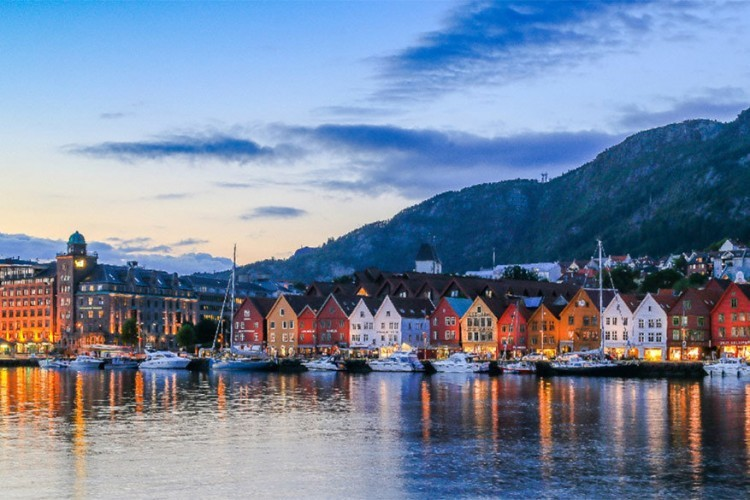 Bergen, Noorwegen: schepen moeten nogal wat zigzaggen rond de verschillende eilanden, inhammen en fjorden om de haven van Bergen te bereiken. Maar eens aangekomen, aanschouw je het Noorwegen dat je kent vanop de postkaarten: gekleurde houten huisjes staan zij aan zij aan de kade, al dan niet met een laagje sneeuw op het dak. Vanaf het dok ben je in 10 minuten in het stadscentrum. © Innovation Norway