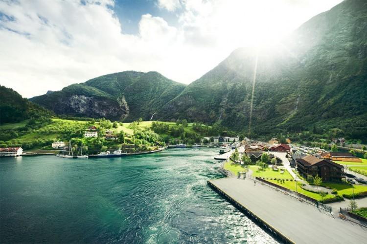Flam, Noorwegen: wie een cruisereis maakt door de Sognefjord in Noorwegen stopt zeker en vast in het petieterige dorpje Flam. Hoge, weelderige groene heuvels, ongeschonden door ontwikkeling, omringen de gedurfde gekleurde huisjes. Het zicht is echt schilderachtig, zowel vanop het dek als vanaf de kade. © pfnphoto.com