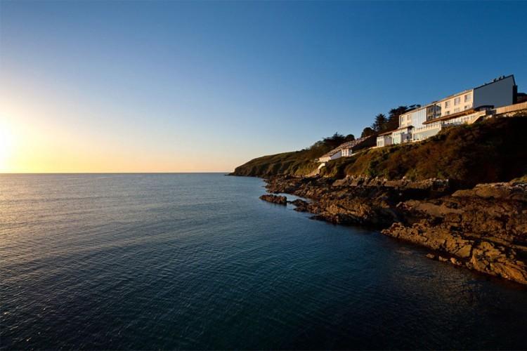The Cliff House Hotel, Ierland: een hotel dat zijn naam niet gestolen heeft. Dit vijfsterrenverblijf ligt letterlijk op een klif aan de zuidkant van Ardmore Bay, vlakbij het Ierse Cork en Waterford. Vanaf je zonovergoten terras en private balkon tuur je naar de kreeften op het strand en de dolfijnen in het water. Geniet er van een smakelijk menu in het met Michelinsterren bekroonde restaurant van het huis of blaas uit in de uitgebreide, strak ingerichte spa. © The Cliff House Hotel