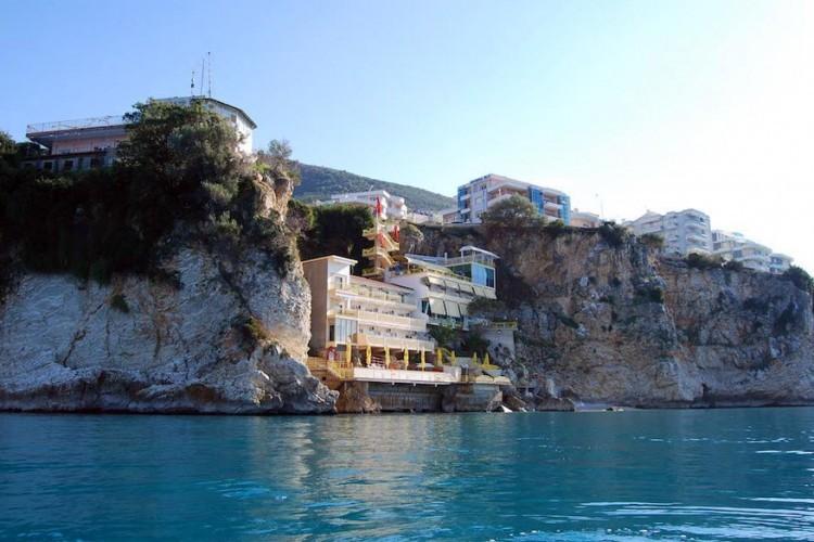 Hotel Liro, Albanië: toegegeven, dit hotel ligt niet letterlijk op een klif, maar er wel vlak tegen. Zit je op een balkon op de hogeren etages, dan glij je best niet van de balustrade af want de afgrond blijft diep genoeg. Hotel Liro, pas gerenoveerd, ligt in de Albanese stad Vlorë in het zuidwesten van het land. Behalve met de verfrissende zeebries en het ongerepte uitzicht pakt het verblijf ook uit met allerhande wateractiviteiten. © Hotel Liro