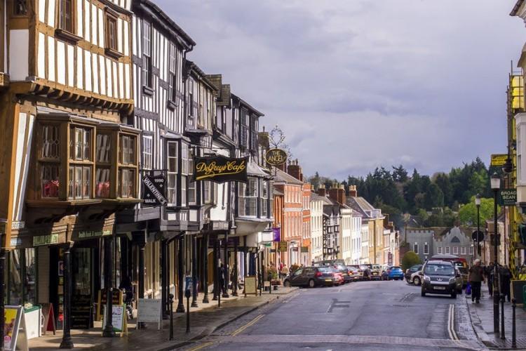 Broad Street in Ludlow, Shropshire: bovenaan deze straat ligt een 18de-eeuws 'buttercross', een soort van afdak waar de mensen van het dorp samenkomen op het marktplein. De weg eindigt met de Broadgate, een middeleeuwse poort met een 18de-eeuws huis bovenop. © Ed Webster via Flickr Creative Commons