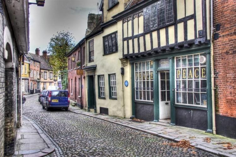 Elm Hill in Norwich, Norfolk: Elm Hill is de best bewaarde middeleeuwse straat in Norwich. Het merendeel van de huizen dateert uit het begin van de 16de eeuw. Een brand verwoestte op een paar na al de woningen waardoor slechts een aantal huizen uit 1507 nog overeind bleven staan. © Peter Munks via Flickr Creative Commons