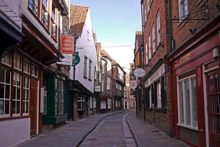 The Shambles in York, Yorkshire: The Shambles in York is een van meest bekende historische straten in Engeland en volgens sommigen ook de best bewaarde middeleeuwse straat. De oudste straat van York dankt zijn naam aan het middeleeuwse woord 'shamel', wat een bank is waarop vlees wordt uitgestald om te verkopen. De tijd maakte er 'Shambles' van. © John Robinson via Flickr Creative Commons