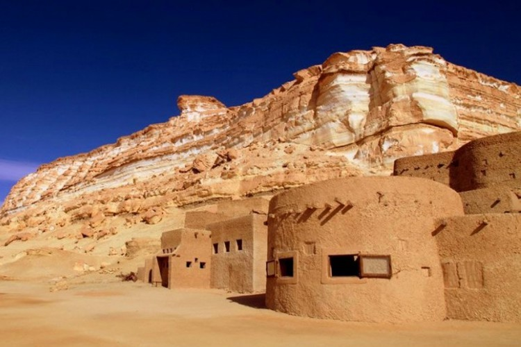 Adrère Amellal in Siwa, Egypte: 8 uur van hoofdstad Caïro vind je in de woestijn van Siwa Adrère Amellal, in de bergen gehouwen eco lodges met 39 slaapkamers. Hier gebruiken ze lantaarns en kaarsen om licht te maken en vuurpotten om het warm te krijgen. De lodges werden vervaardigd uit steen, zout, water en klei en versmelten mooi in het rotsachtige landschap. De moderne badkamers en comfortabele bedden buiten beschouwing gelaten lijkt het wel of de tijd hier heeft stil gestaan. © Kiwi Collection