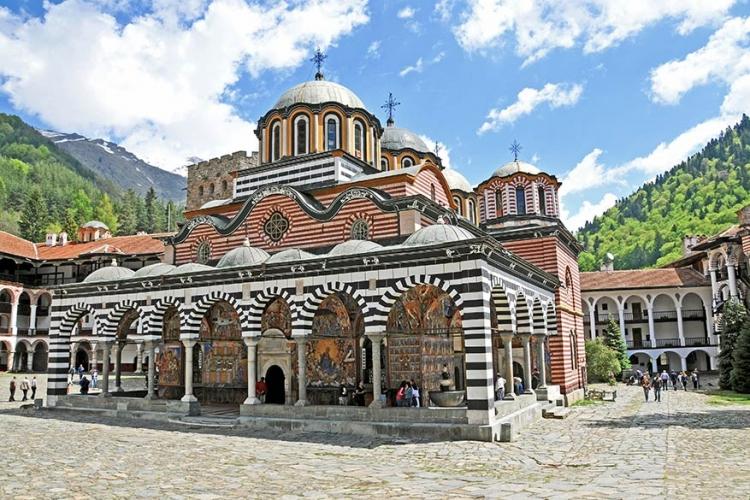 """Rikaklooster in Bulgarije: 1.147 meter hoog in het onherbergzame Rikagebergte vind je dit """"klooster met zebrahuid"""". Al sinds de 10de eeuw is dit kleurrijk klooster een bedevaartsoord. © Wikimedia Commons"""