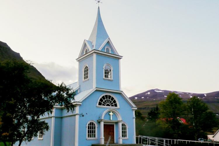 """Blauwe kerk in Seyoisfjorour, IJsland: in een klein stadje aan de fjorden in IJsland, omringd door watervallen en bergen staat een pittoresk blauw kerkje. Om het makkelijk te maken wordt deze kerk ook dan gewoon """"de blauwe kerk"""" genoemd! © CaptainOates via Flickr Creative Commons"""